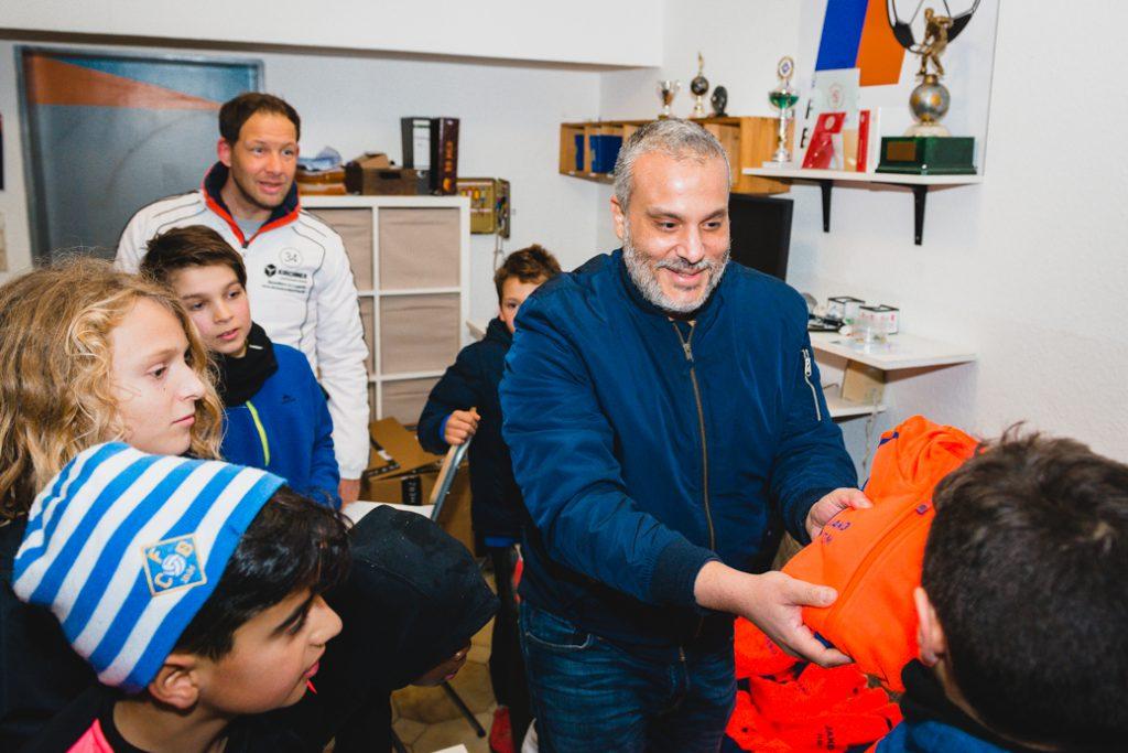 Dr. Karim Zayed verteilt die Outfits an begeisterte Fussballer